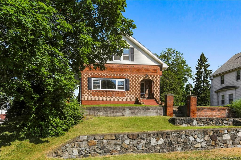 Lives like a THREE BEDROOM!  Classic brick colonial sits perched on a hill on a large lot and offers
