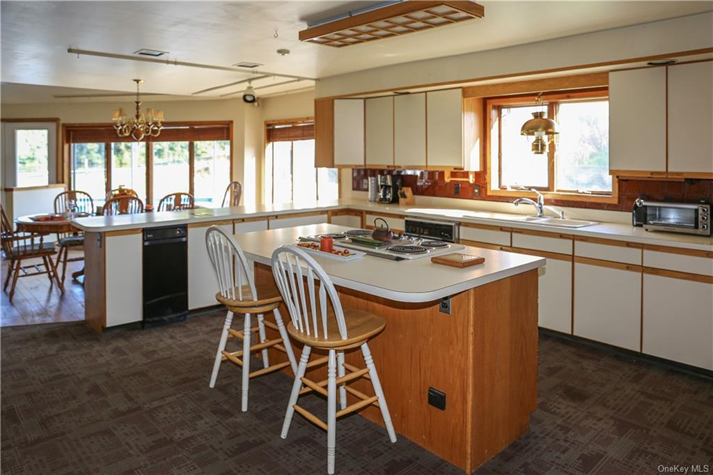 The kitchen is open to the dining room and features an island with cooktop and plenty of cabinet space