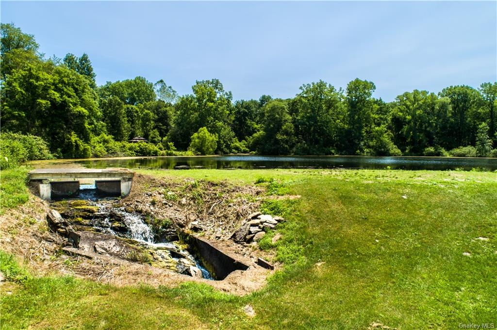 Park-like level lawn surrounds the gazebo at the other end of the pond.