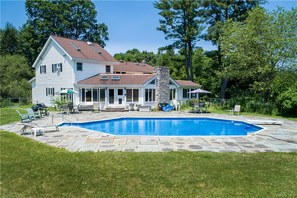 Fenced in, in-ground pool with patio surround.
